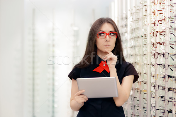 Stock photo: Undecided Woman with PC Tablet in Optical Store