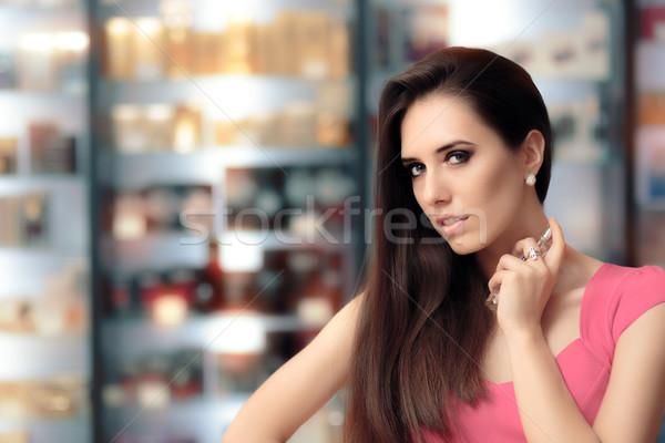 Beautiful Girl Testing Perfume in a Cosmetics Shop Stock photo © NicoletaIonescu