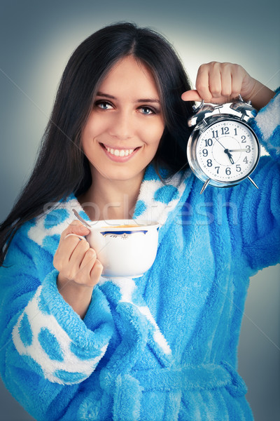 Young Woman in Bathrobe Holding an Alarm Clock and a Cup of Coffee  Stock photo © NicoletaIonescu