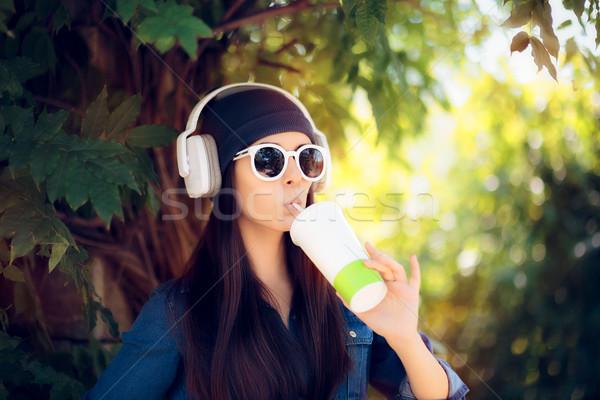 Hideg lány farmer visel napszemüveg iszik Stock fotó © NicoletaIonescu