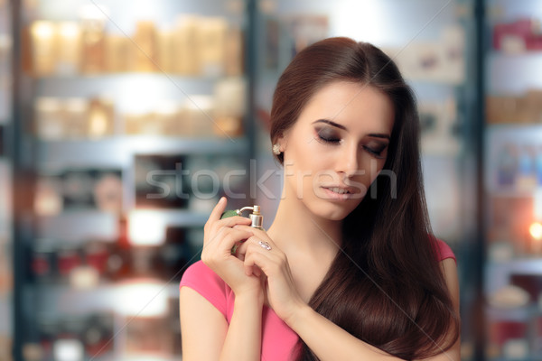Beautiful Girl Testing Perfume in a Cosmetics Shop Stock photo © NicoletaIonescu