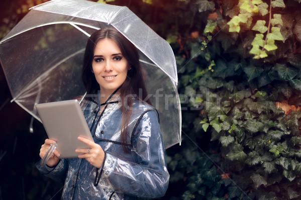 Glimlachende vrouw regenjas paraplu pc tablet Stockfoto © NicoletaIonescu