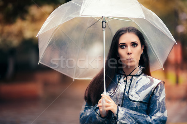 Funny Woman with Transparent Raincoat and Umbrella Stock photo © NicoletaIonescu