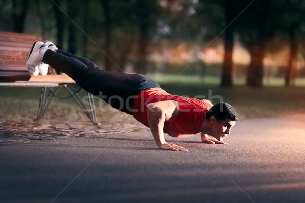 Fitness man bank druk omhoog buiten Stockfoto © NicoletaIonescu