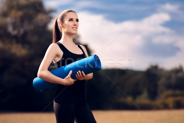 Pilates Girl with Yoga Mat Standing Outdoor in Nature Stock photo © NicoletaIonescu