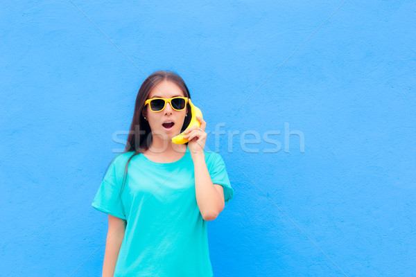 Funny Girl with Sunglasses and Banana Phone on Blue Background Stock photo © NicoletaIonescu