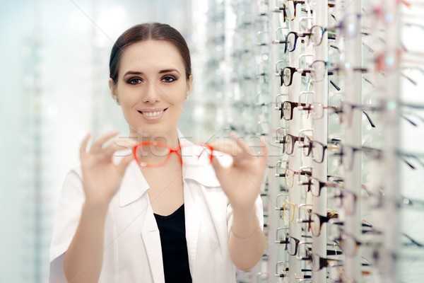 Happy Optician Handing Over  Eyeglasses for a Try Out Stock photo © NicoletaIonescu