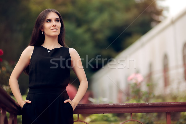 Elegant Woman Wearing Black Dress Standing in a Patio Stock photo © NicoletaIonescu