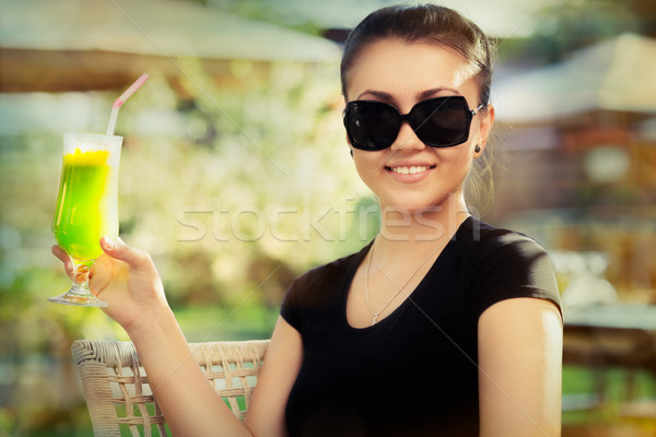 Young Woman with Sunglasses and Colorful Cocktail Drink Outside  Stock photo © NicoletaIonescu