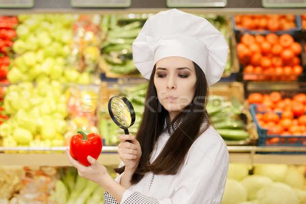 Stock photo: Concerned  Lady Chef Inspecting Vegetables with Magnifying Glass