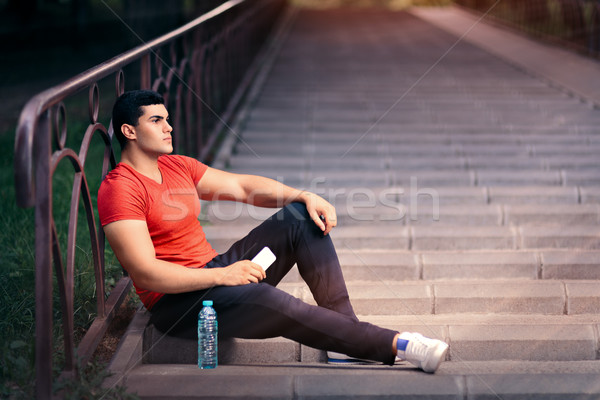 Fit Man Resting with Water Bottle and Phone Stock photo © NicoletaIonescu
