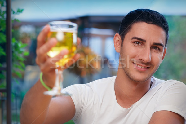 Young Man Rising a Glass in a Bar Stock photo © NicoletaIonescu