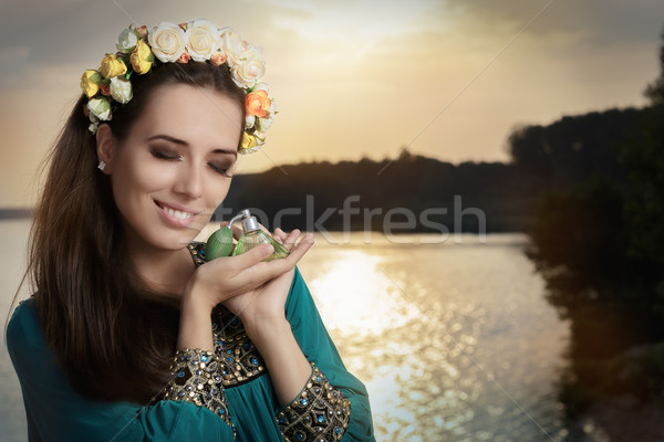 Young Woman Holding Perfume Bottle in Sunlight   Stock photo © NicoletaIonescu