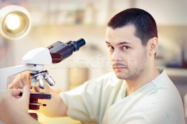 Vicces fiatal férfi tudós mikroszkóp portré Stock fotó © NicoletaIonescu