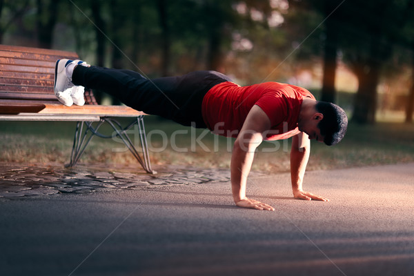 Fitness Man doing a Bench Press Up Outside Stock photo © NicoletaIonescu