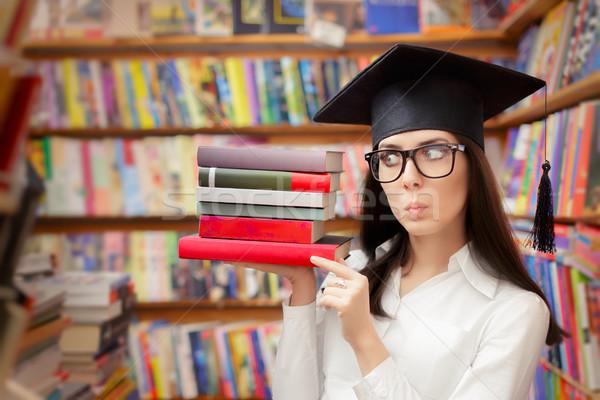 Surprised  Student with Graduation Cap Holding Books Stock photo © NicoletaIonescu