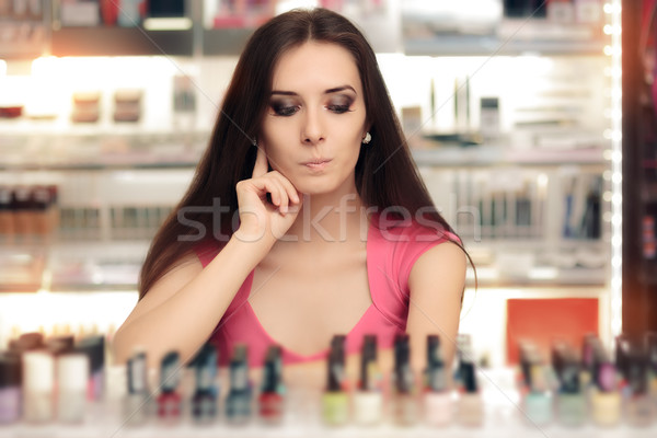 Cute Girl Choosing Between Bottles of Nail Polish Stock photo © NicoletaIonescu