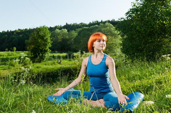 Red woman practicing fitness yoga outdoors Stock photo © nikitabuida