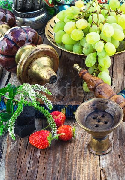 Hookah amid bunches of grapes and strawberries Stock photo © nikolaydonetsk