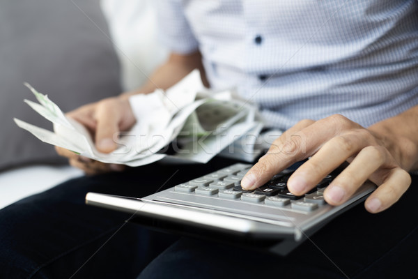 young man with bills and calculator Stock photo © nito