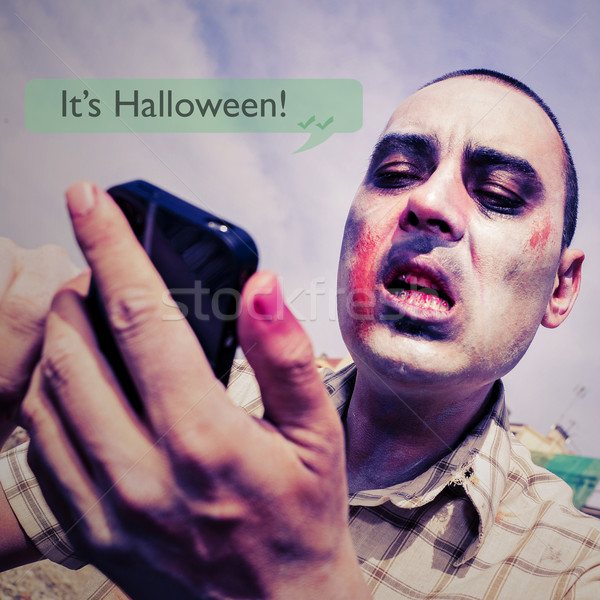zombie with a smartphone and the text message it is halloween Stock photo © nito