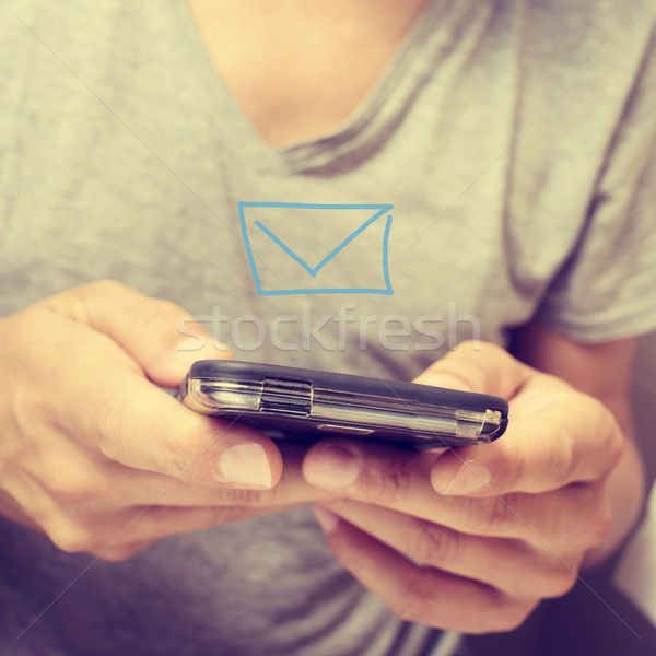 young man sending or receiving a text message Stock photo © nito