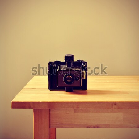 Stock photo: old instant camera on a bureau
