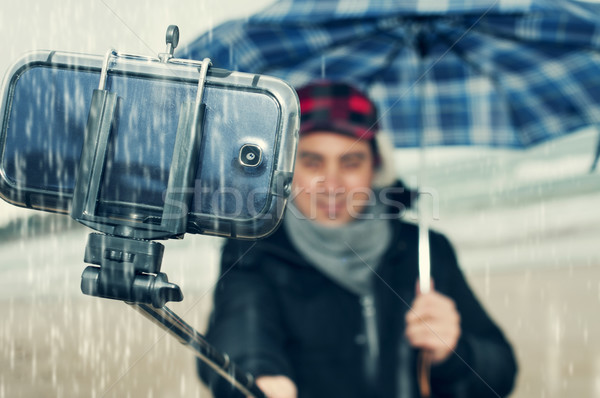 young man taking a selfie under the rain Stock photo © nito