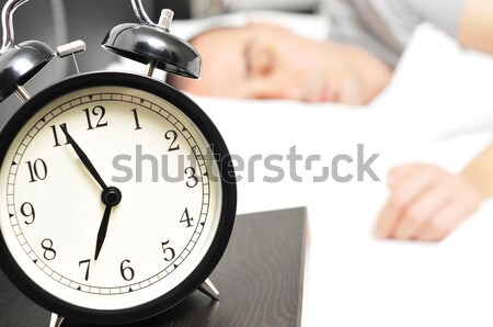 alarm clock and young man sleeping in bed Stock photo © nito