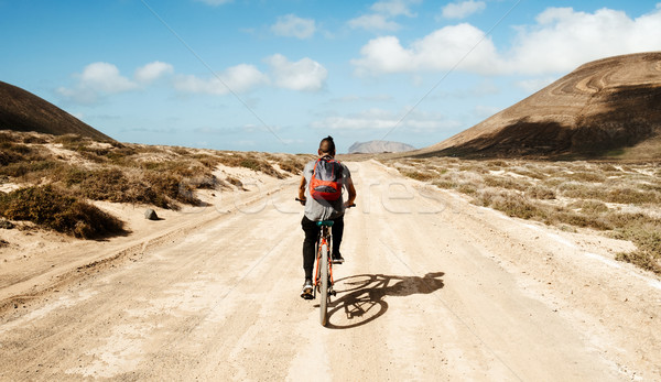 Stock photo: man riding a bike in La Graciosa, Canary Islands, Spain
