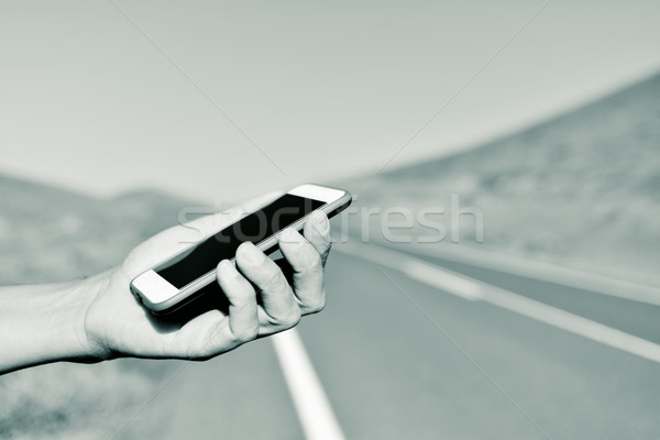 man using a smartphone next to the road Stock photo © nito