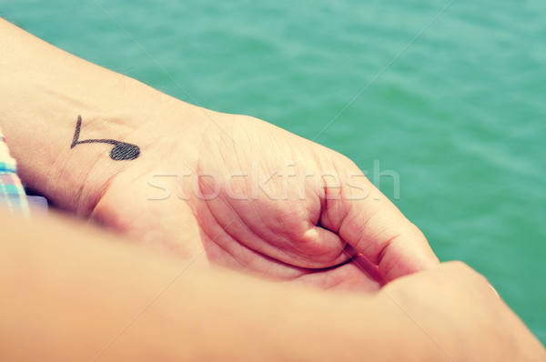 a young man with a musical note tattooed in his wrist Stock photo © nito