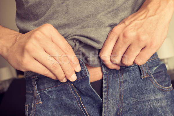 young man trying to fasten his trousers Stock photo © nito