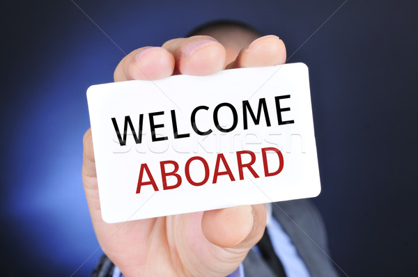man with a signboard with the text welcome aboard Stock photo © nito