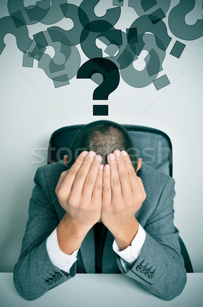 businessman with his hands in his head and question marks Stock photo © nito