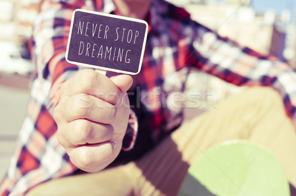 young man with a signboard with the text never stop dreaming Stock photo © nito
