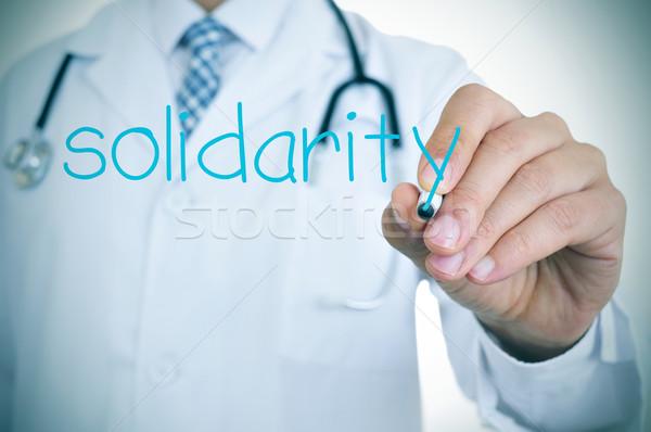 Médico escrito palabra solidaridad primer plano jóvenes Foto stock © nito