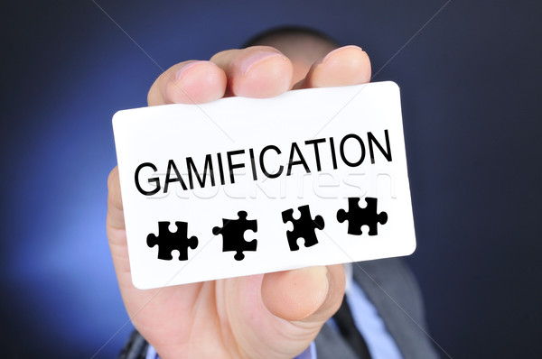 young man in suit shows a signboard with the word gamification Stock photo © nito