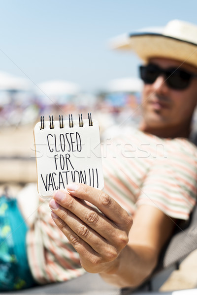 man with a note with the text closed for vacation Stock photo © nito