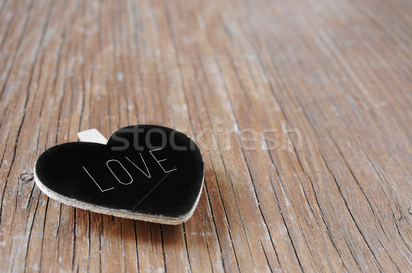 heart-shaped chalkboard with the word love on a rustic wooden su Stock photo © nito