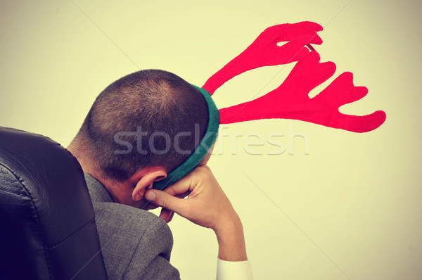 man with a reindeer antlers headband in his office chair, with a Stock photo © nito
