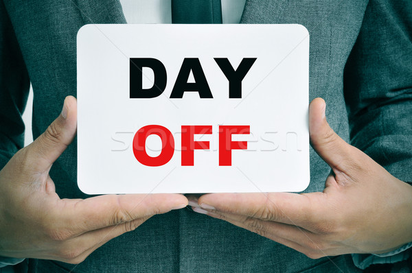 businessman with a signboard with the text day off Stock photo © nito