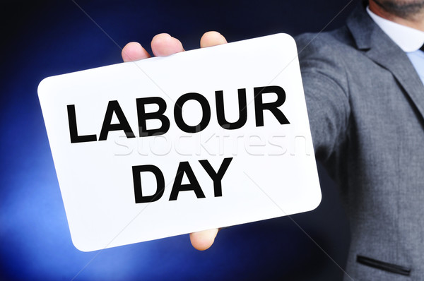man showing a signboard with the text labour day Stock photo © nito