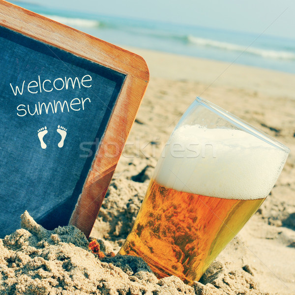 beer and chalkboard with the text welcome summer, on the sand of Stock photo © nito