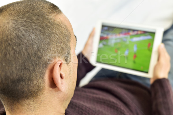 young man watching a soccer match in his tablet Stock photo © nito