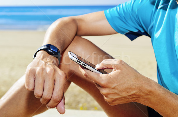 young sportsman syncing his smartwatch Stock photo © nito