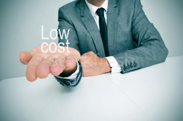 Olcsó üzletember ül asztal mutat szöveg Stock fotó © nito