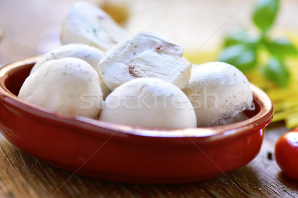 fresh mushrooms in an earthenware bowl on a wooden table Stock photo © nito