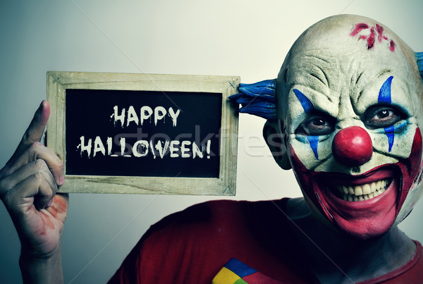 evil clown with a chalkboard with the text happy Halloween Stock photo © nito