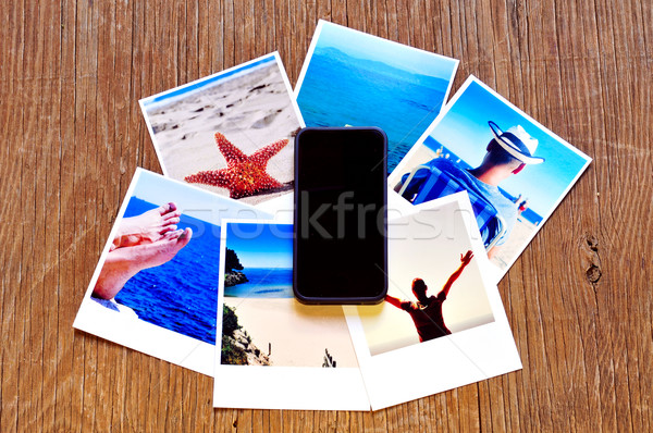 smartphone and some photos on a wooden surface Stock photo © nito